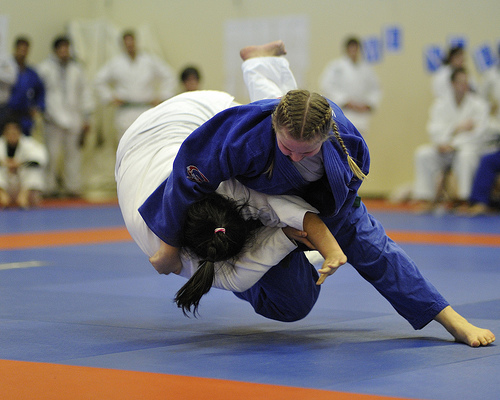 Two martial artists grappling towards a submission in a karate bout.