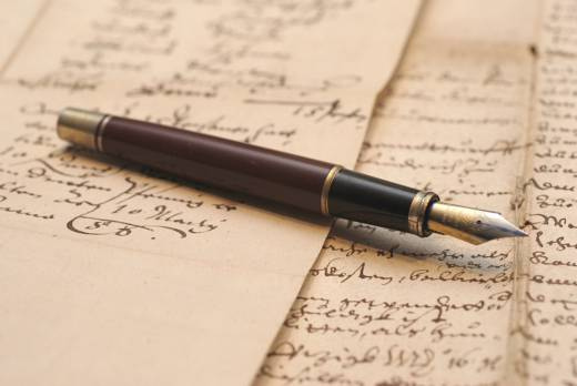 A fountain pen resting on sheets of parchment